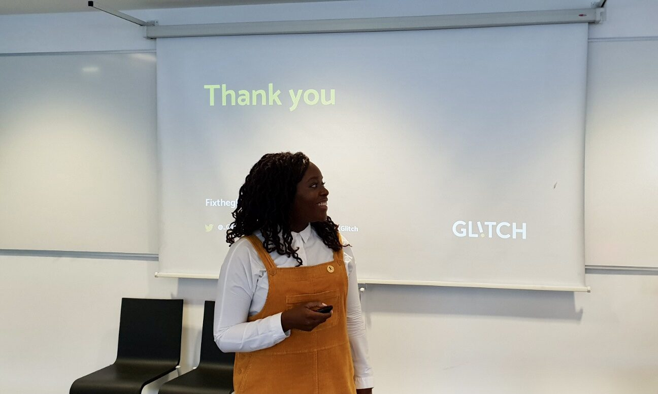 Seyi, a black woman wearing a white and yellow top, is standing in front of a screen which contains the Glitch logo. She's smiling at someone out of shot.